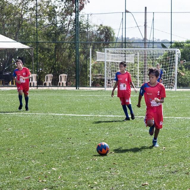Crianças jogando futebol com uniforme do Instituto Ramacrisna