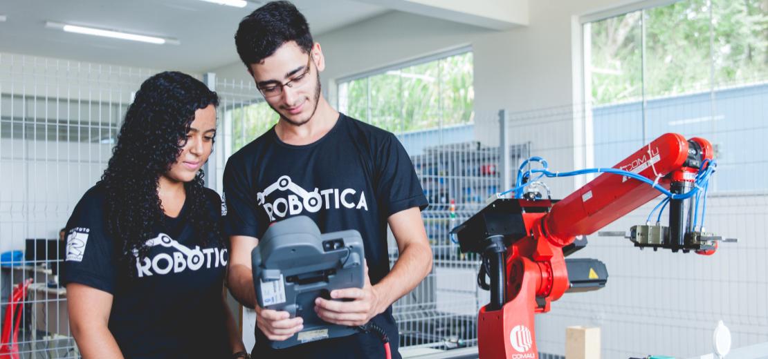 Casal de jovens com camisa do curso observando o equipamento