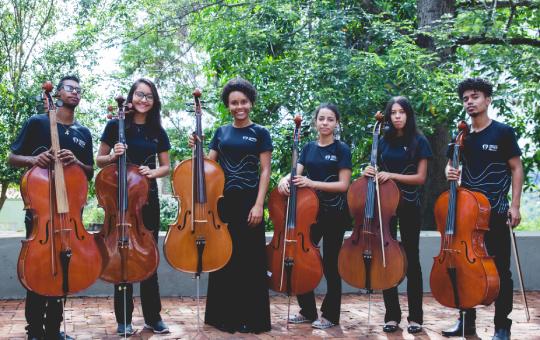 Integrante da orquestra, de pé, segurando violoncelos