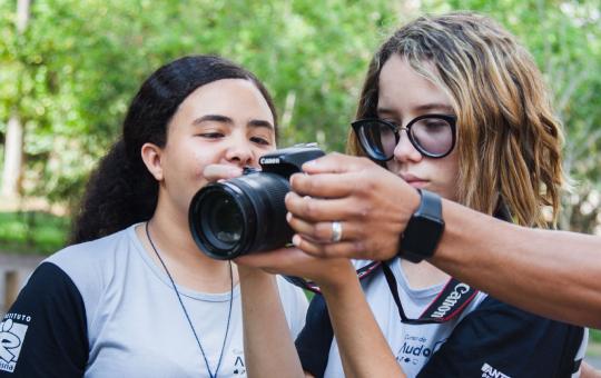 Mão do professor segurando a câmera diante de duas alunas que observam a tela