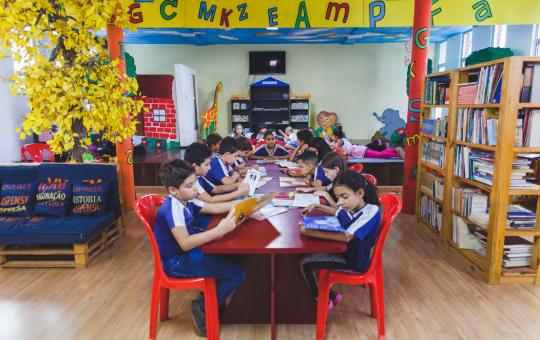 Crianças sentadas numa mensa no meio da biblioteca, lendo.
