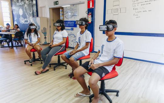 Alunos sentados em cadeiras com óculos de realidade virtual