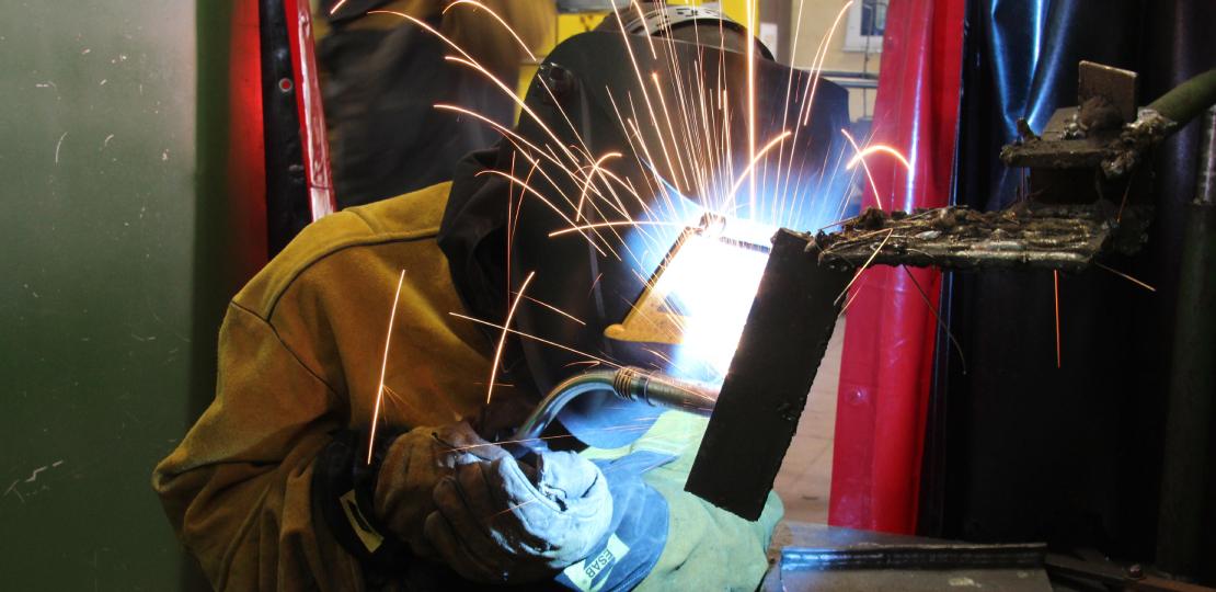 Aluno do curso soldando peças com capacete e equipamentos de segurança