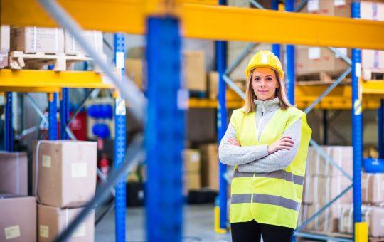 Mulher de braços crusados em ambiente de trabalho, setor de armazenamento.