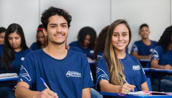 dois jovens aprendizes do instituto Ramacrisna sentados em uma mesa de sala de aula do curso de aprendizagem