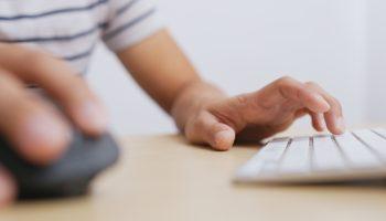 mão mexendo no teclado e no mouse, em cima de uma mesa
