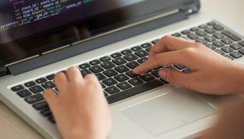 Duas mãos digitando em um teclado, simbolizando o curso gratuito de programação em PLC do Instituto Ramacrisna,