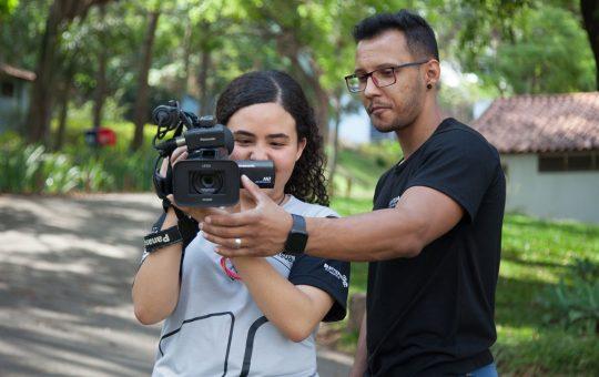 Menina com a câmera apontada para frente, seguindo orientações de professor