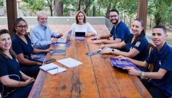 membros do GIP, sentados em uma mesa de madeira grande, discutindo sobre projetos e sorrindo