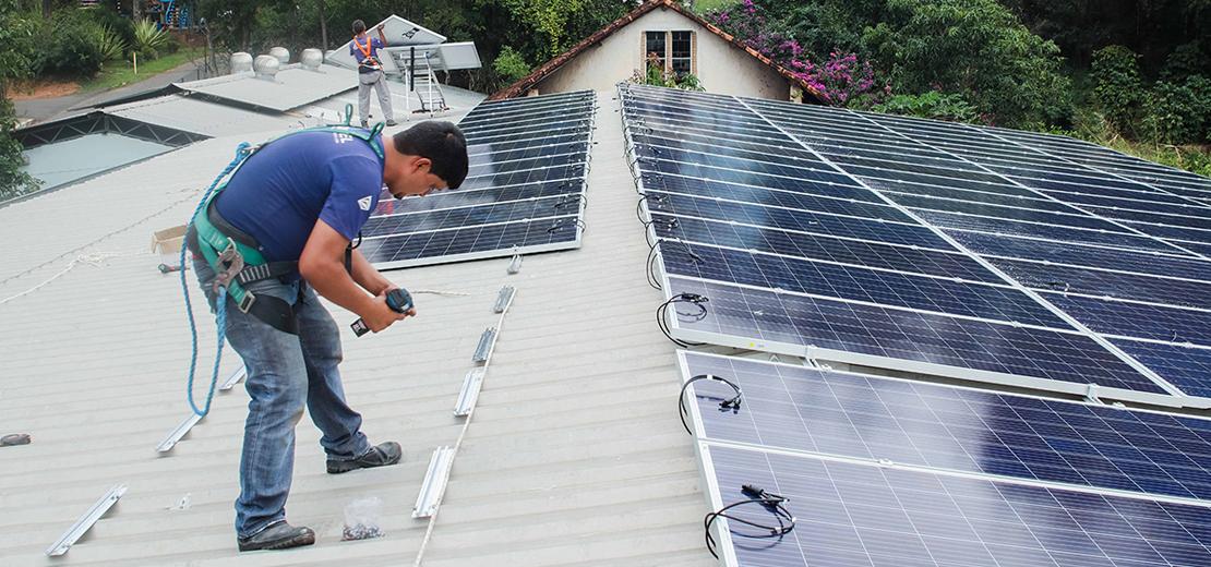 Aluno instalando placa fotovoltaica durante curso