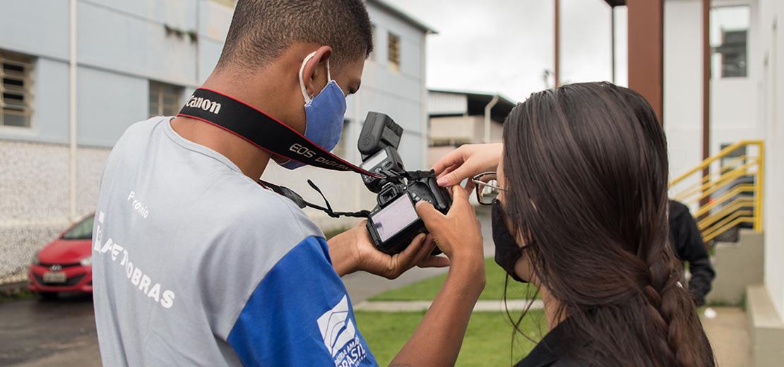 Jovem com câmera na mão e professora instruindo em curso profissionalizante