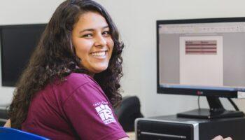 aluna do programa de aprendizagem do Ramacrisna, sentada na frente de um computador e sorrindo