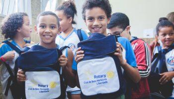 Grupo de crianças em uma sala. As duas da frente sorriem, enquanto exibem suas mochilas do Rotary Club. Imagem do artigo sobre o Dia do Rotariano.