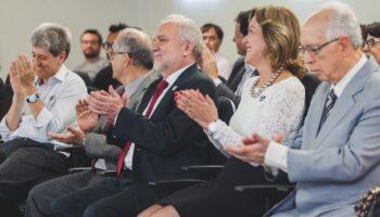 Membros da organização sentados, sorrindo e aplaudindo.