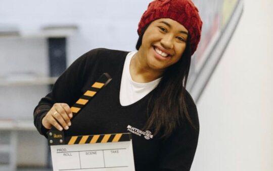 Cleidiane sorrindo e segurando uma placa de direção de cinema