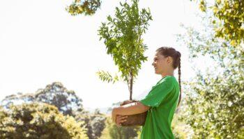 menina numa área verde segurando um vaso com uma árvore pequena nos braços