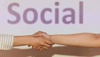 Aperto de mãos com a palavra Social, ao fundo, exibida em um telão. Capa do blogpost sobre parceria com ONGs.