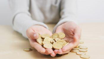 Duas mãos segurando moedas, simbolizando o blogpost sobre mitos e verdades das doações no Brasil.