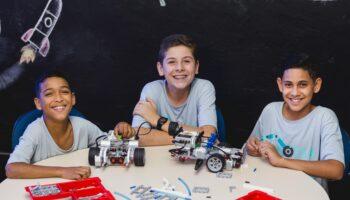 Três jovens posando para a foto durante uma aula de oficina robótica de um projeto para adolescentes.