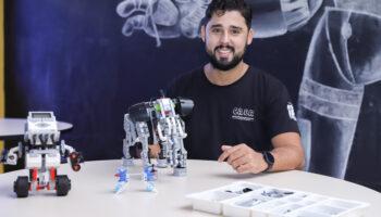 Geisibel Castro, gestor do Ramacrisna, sentando em uma mesa, com um robô em frente.