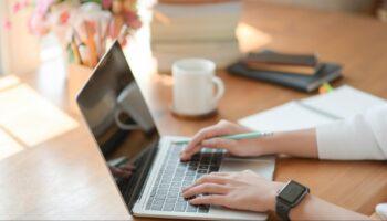 Duas mãos digitando em um computador fazendo doações do imposto de renda, com uma xícara de café ao fundo.