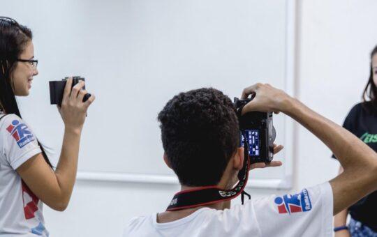 Dois jovens filmando e tirando fotos de uma mulher.