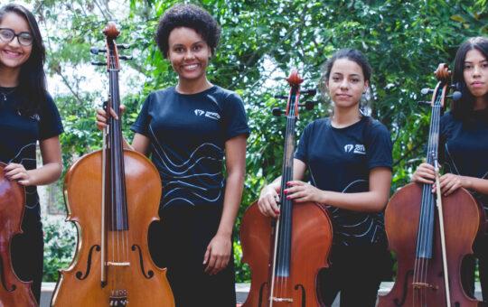 Grupo de seis jovens da Orquestra Jovem Ramacrisna. Cada um segura um violoncelo.