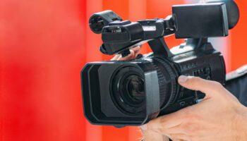 Uma mão segurando uma câmera, com um cenário vermelho ao fundo.