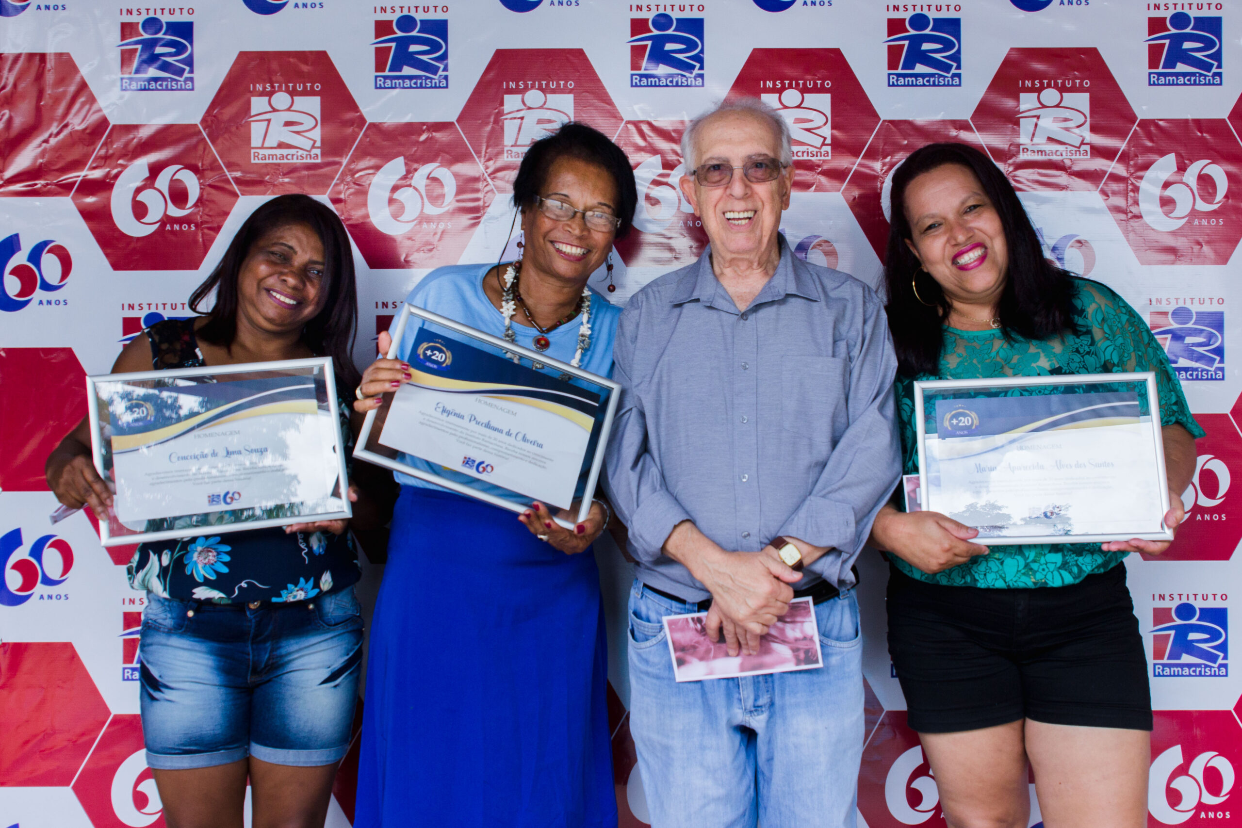 Três mulheres e um homem na foto. Dentre eles, Dona Efigênia recebendo homenagem por mais de 20 anos de Ramacrisna.