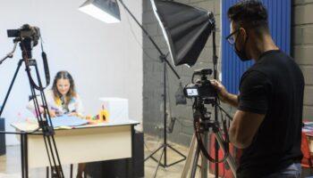 Imagem mostra cinegrafista de máscara com uma camêra e uma mulher em uma mesa sendo gravada. O cenário de como gravar aulas on-line.