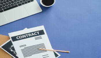 Imagem mostra teclado de notebook, um copo de café, e uma folha de contrato com um lápis.