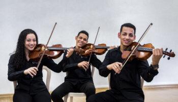 Três adolescentes, da Orquestra Jovem Ramacrisna que recebe verba do Projeto Hotmart UmPorCento, sentados tocando violino.