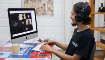 Instrutor do Ramacrisna em frente ao computador em uma aula on-line nos cursos para jovem aprendiz.