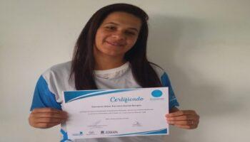 Aluna do projeto Ampliando Fronteiras segurando o certificado do curso.