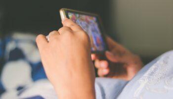 Imagem mostra mãos segurando um celular, fazendo alusão de um aluno assistindo lives do Ramacrisna.