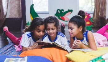 Crianças compartilhando livro na Biblioteca do Instituto Ramacrisna. Educação de qualidade é um dos Objetivos do Desenvolvimento Sustentável
