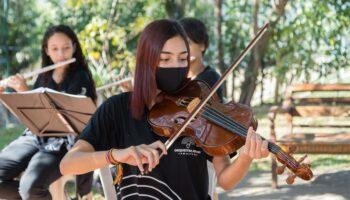 Mulher tocando violino durante apresentação da Orquestra Jovem, durante a pandemia. Ao fundo, dois outros músicos tocam flauta.