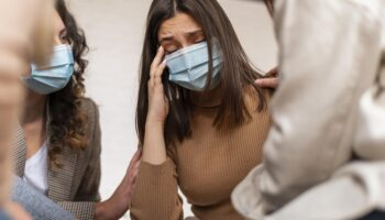 Mulher usando máscara com mão na testa. Ela tem uma expressão de tristeza. Imagem representa o estresse e o cansaço, problemas de saúde mental na pandemia