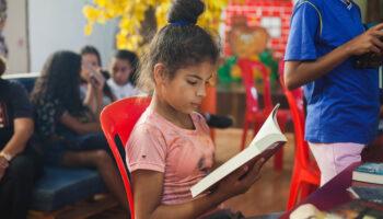 Menina com livro na mão. Ela está de cabelo preso. Ao fundo, outras crianças também segurando livros infanto-juvenis