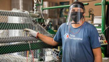 Funcionário da Fábrica de Telas Ramacrisna operando o maquinário. Ele usa máscara de proteção e face shield