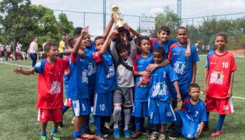 Time do Instituto Ramacrisna levantando um troféu. Eles estão no campo e usando uniformes de futebol, uma das modalidades de esporte para crianças