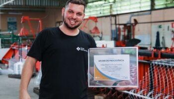 Octávio Figueiredo segurando um certificado de qualidade das telas ramacrisna