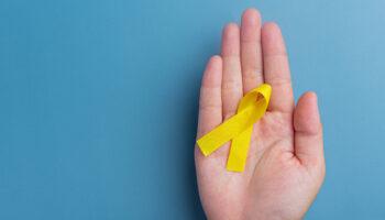 Mão segurando um laço amarelo, símbolo da campanha Setembro Amarelo
