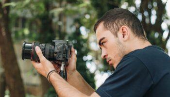 Funcionário da produtora audiovisual manuseando uma câmera fotográfica profissional